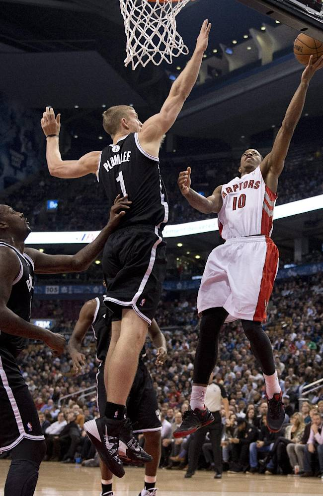 Toronto Raptors guard DeMar DeTozan (10) drives to the hoop against Brooklyn Nets forwards Andray Blatche, left, and Mason Plumlee (1) during the first half of an NBA basketball game in Toronto on Tuesday, Nov. 26, 2013