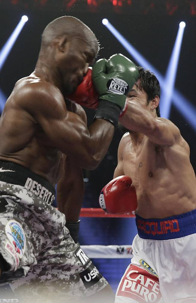 Manny Pacquiao, right, of the Philippines, lands a left to the face of Timothy Bradley, in their WBO welterweight title boxing fight Saturday, April 12, 2014, in Las Vegas. Pacquiao won the bout by unanimous decision