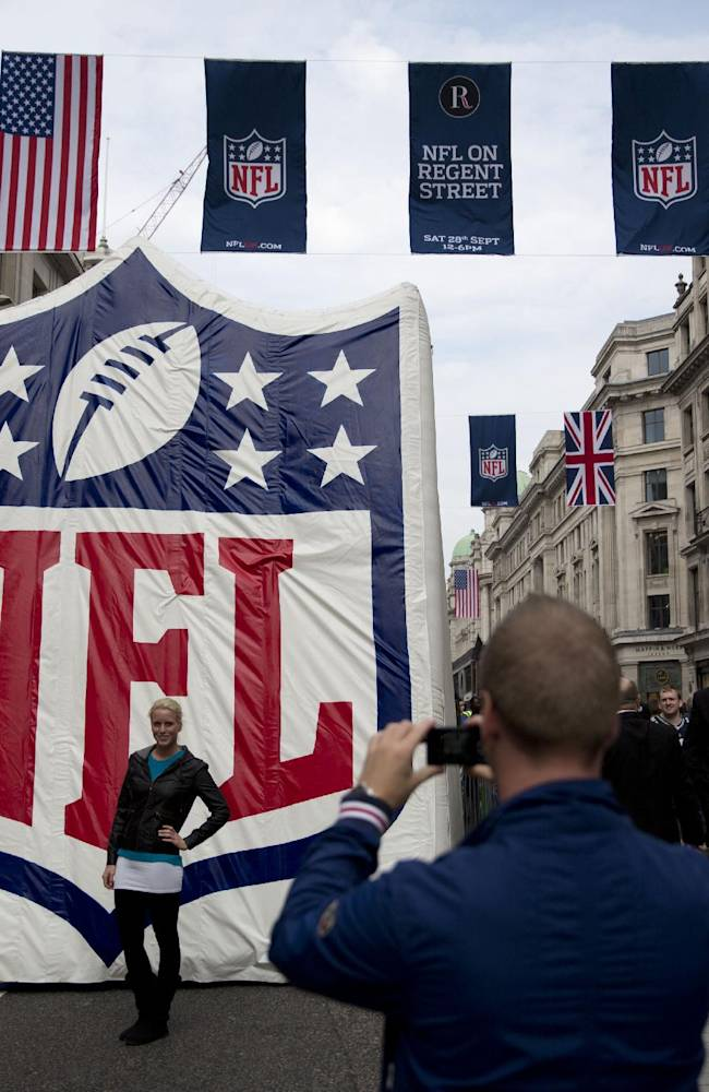 A woman poses for a picture during a NFL fan rally event in Regent Street, London, Saturday, Sept. 28, 2013.  The Minnesota Vikings are to play the Pittsburgh Steelers at Wembley stadium in London on Sunday, Sept. 29 in a regular season NFL game