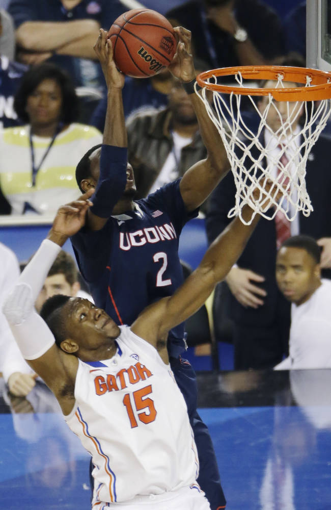 Connecticut forward DeAndre Daniels (2) controls the ball as Florida forward Will Yeguete (15) defends during the second half of the NCAA Final Four tournament college basketball semifinal game Saturday, April 5, 2014, in Arlington, Texas
