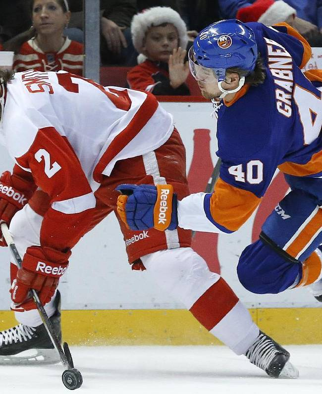 Detroit Red Wings defenseman Brendan Smith (2) takes New York Islanders right wing Michael Grabner (40), of Austria, off the puck in the first period of an NHL hockey game, Monday, Dec. 23, 2013, in Detroit