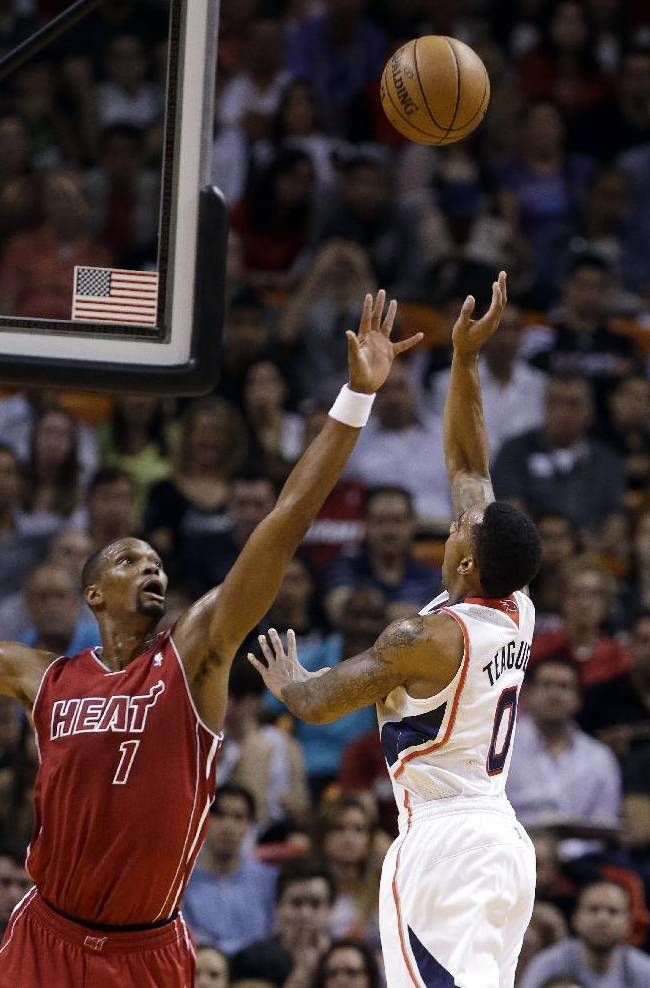 Atlanta Hawks' Jeff Teague (0) shoots over Miami Heat's Chris Bosh (1) in the first half of an NBA basketball game, Monday, Dec. 23, 2013, in Miami