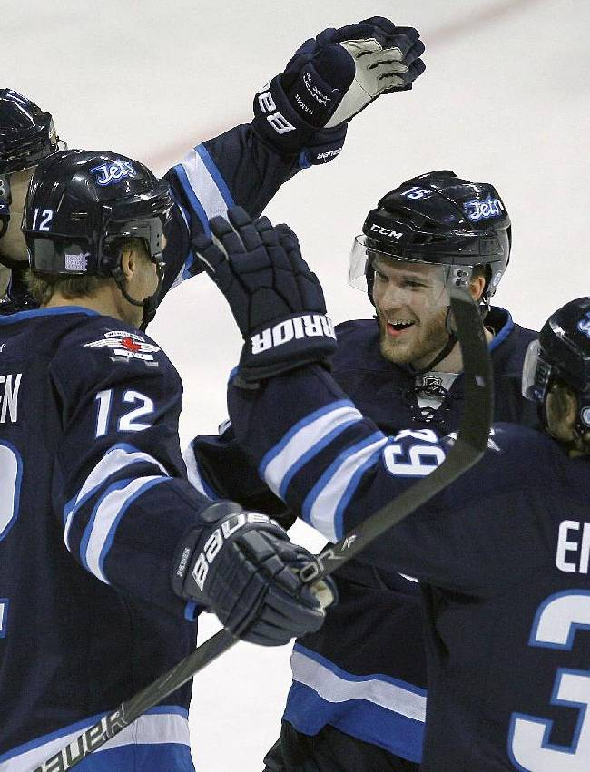 Winnipeg Jets' James Wright (17), Olli Jokinen (12), Matt Halishchuk (15) and Toby Enstrom (39) celebrate Jokinen's goal against the St. Louis Blues during the first period of an NHL hockey game, Friday, Oct. 18, 2013 in Winnipeg, Manitoba
