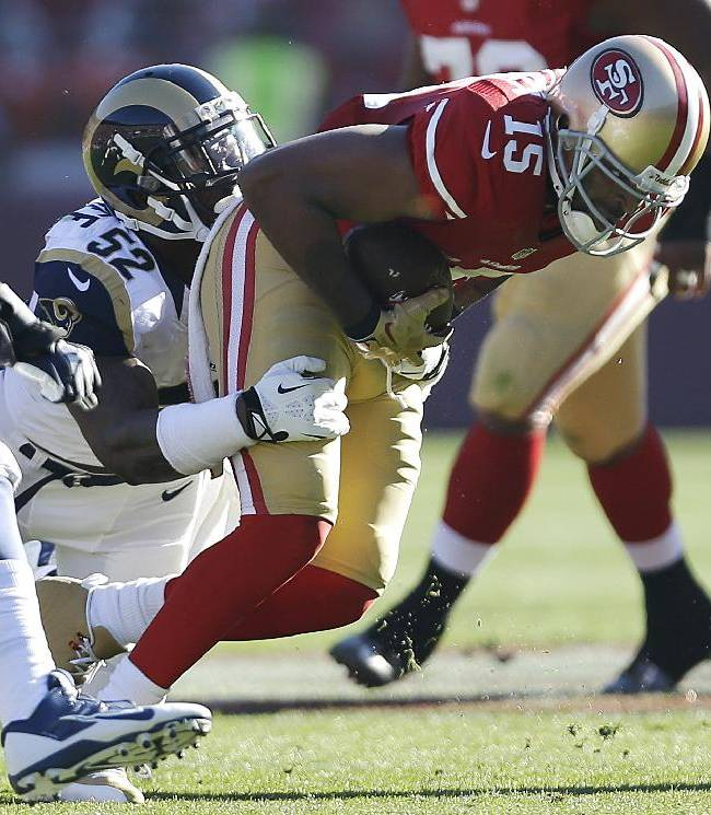 San Francisco 49ers wide receiver Michael Crabtree (15) is tackled by St. Louis Rams outside linebacker Alec Ogletree (52) after a reception during the first half of an NFL football game in San Francisco, Sunday, Dec. 1, 2013