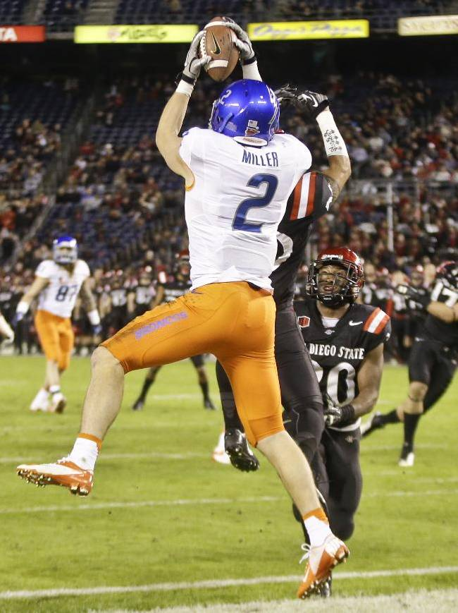 Boise State wide receiver Matt Miller catches a 10 yard touchdown pass over a San Diego State defender during the fourth quarter of an NCAA college football game Saturday, Nov. 23, 2013, in San Diego. San Diego State won the game 34-31 in overtime