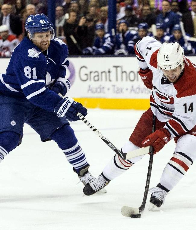 Carolina Hurricanes' Nathan Gerbe, right, gets a shot away as Toronto Maple Leafs' Phil Kessel defends during the first period of an NHL hockey game, Sunday, Dec. 29, 2013, in Toronto