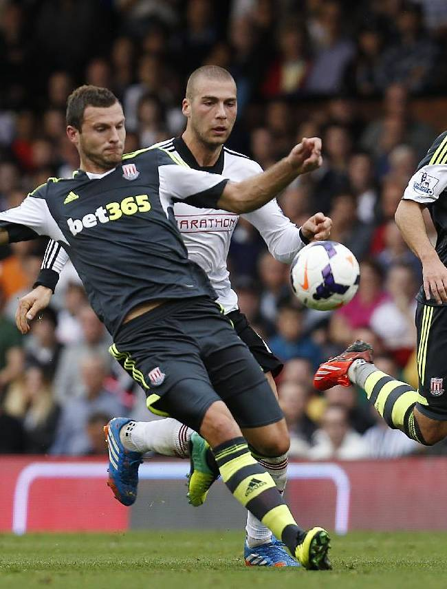 Stoke City's Erik Pieters, left, tries to control the ball in front of Fulham's Pajtim Kasami, center, as his teammate Matthew Etherington, right, looks on during an English Premier League soccer match at the Craven Cottage ground in London, Saturday, Oct. 5, 2013. Fulham won the match 1-0