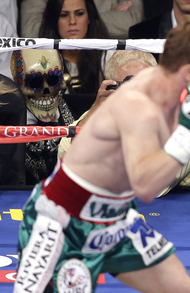 In this photo taken, Sept. 14, 2013, boxing judge Cynthia C.J. Ross, left, watches as Canelo Alvarez throws a jab at Floyd Mayweather Jr. during a world junior middleweight title fight in Las Vegas. Ross is temporarily stepping away from the ring after drawing widespread criticism for scoring the fight a draw when two other judges scored Mayweather the clear winner