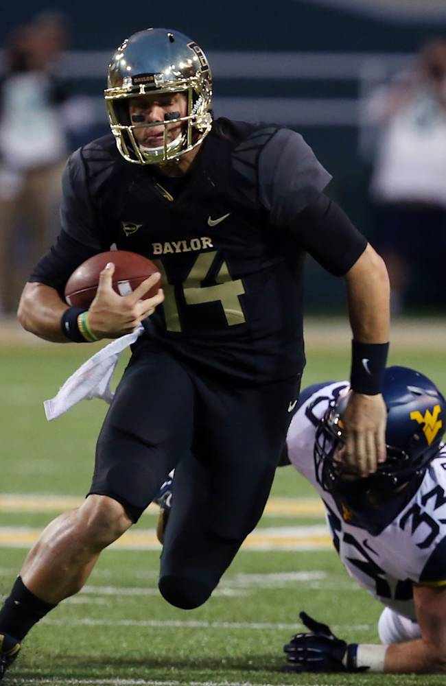 Baylors Bryce Petty (14), left, runs for extra yardage past West Virginia linebacker Jared Barber (33), right, during the first half of an NCAA college football game on Saturday, Oct.  5, 2013, in Waco, Texas
