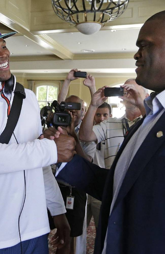 Carolina Panthers' Cam Newton, left, congratulates Travelle Wharton at Wharton's retirement news conference during an NFL football practice at their training camp in Spartanburg, S.C., Tuesday, July 29, 2014