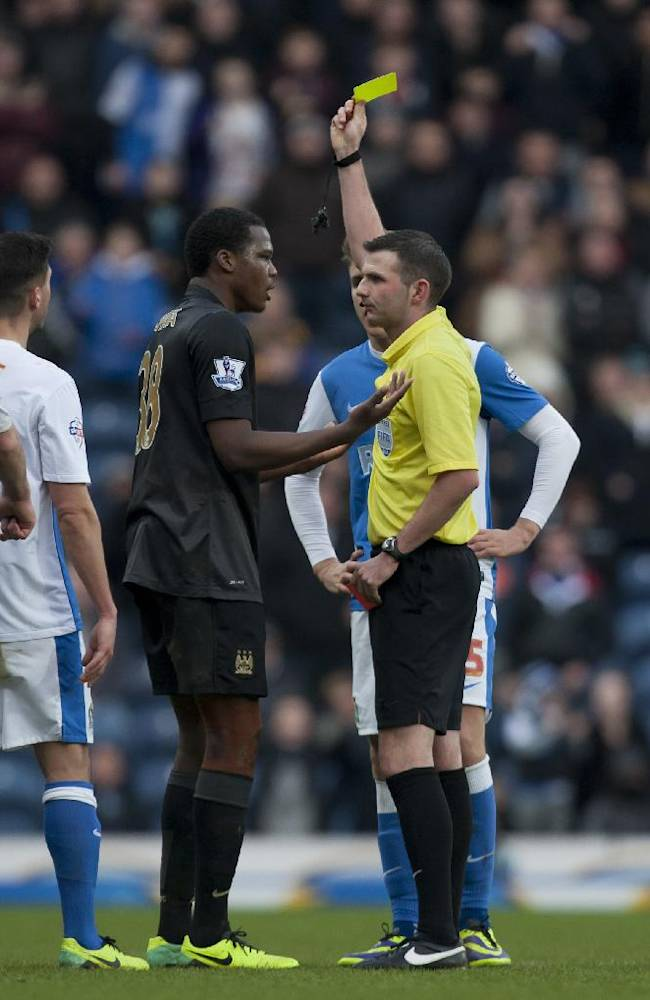 Manchester City's Dedryck Boyata is shown a second yellow card by referee Michael Oliver during his team's English FA Cup third round soccer match against Blackburn Rovers at Ewood Park Stadium, Blackburn, England, Saturday, Jan. 4, 2014