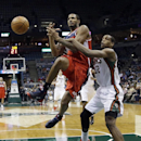 Milwaukee Bucks' Khris Middleton, right, fouls Washington Wizards' Trevor Ariza as he goes up for a shot during the first half of an NBA basketball game Wednesday, Nov. 27, 2013, in Milwaukee The Associated Press