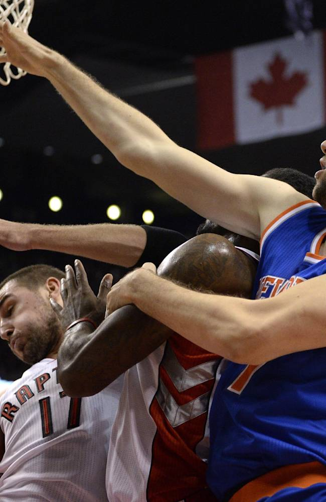 Toronto Raptors' Jonas Valanciunas, left, and teammate Amir Johnson, center, battle with New York Knicks' Andrea Bargnani, right, during first-quarter NBA basketball preseason game action in Toronto, Friday, Oct. 11, 2013
