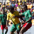 South Africa's Lerato Chabangu, left, is challenged by Burkina Faso's Issouf Dayo, right, during their Nelson Mandela Sports and Cultural Day soccer match at Soccer City Stadium in Johannesburg, South Africa, Saturday, Aug. 17, 2013. (AP Photo/Themba Hadebe)