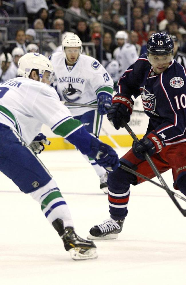 Columbus's Marian Gaborik (10), of Slovakia, shoots as Vancouver's Ryan Stanton, left, defends during the second period of an NHL hockey game Sunday, Oct. 20, 2013, in Columbus, Ohio