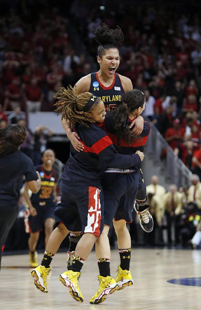 Maryland forward Alyssa Thomas, top,celebrates with guard Sequoia Austin, left, and another player after Maryland defeated Louisville 76-73 in a regional final of the NCAA women's college basketball tournament Tuesday, April 1, 2014, in Louisville, Ky