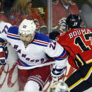 New York Rangers' Dan Boyle, left, dodges a check from Calgary Flames' Lance Bouma during the first period of an NHL hockey game in Calgary, Alberta, Tuesday, Dec. 16, 2014. (AP Photo/The Canadian Press, Jeff McIntosh)