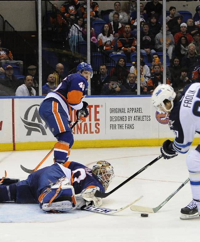 New York Islanders goalie Kevin Poulin (60) dives to block a shot on goal by Winnipeg Jets' Michael Frolik (67) as Matt Martin (17) defends from behind in the third period of an NHL hockey game on Wednesday, Nov. 27, 2013, in Uniondale, N.Y. The Jets won 3-2