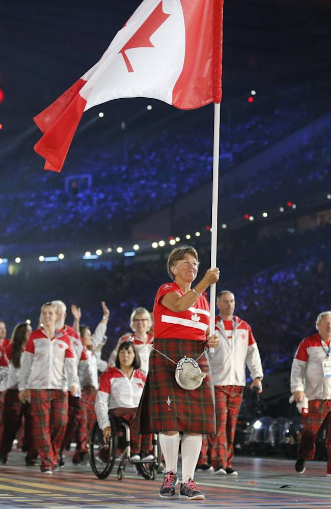 Canada's flag bearer Susan Nattrass leads the team into the arena during the opening ceremony for the Commonwealth Games 2014 in Glasgow, Scotland, Wednesday July 23, 2014
