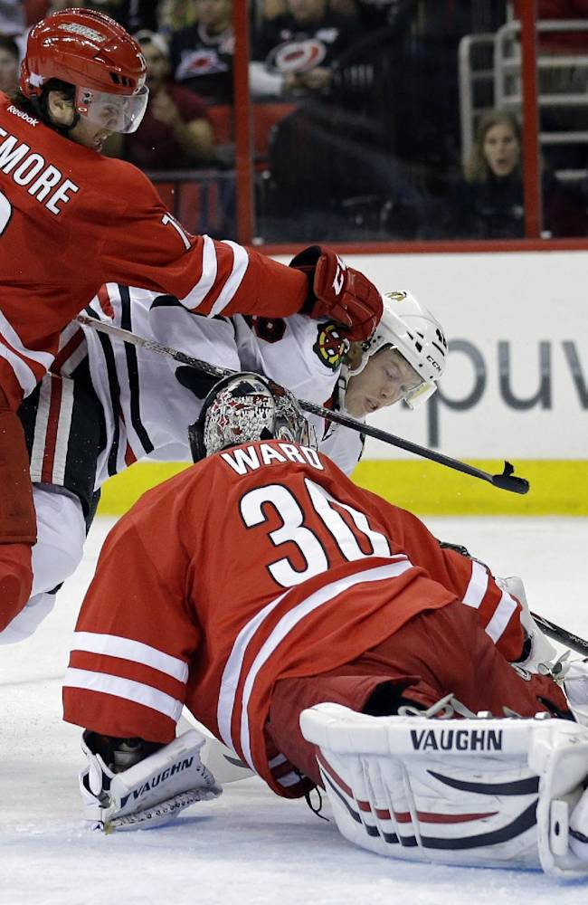 Chicago Blackhawks' Joakim Nordstrom, center, of Sweden, tries to shoot as Carolina Hurricanes' Brett Bellemore (73) and goalie Cam Ward (30) defend during the first period of an NHL hockey game in Raleigh, N.C., Tuesday, Oct. 15, 2013