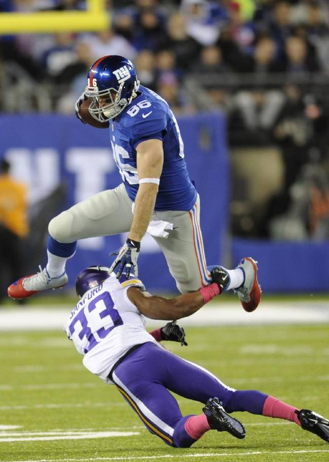 New York Giants tight end Bear Pascoe (86) leaps over Minnesota Vikings' Jamarca Sanford (33) during the first half of an NFL football game Monday, Oct. 21, 2013 in East Rutherford, N.J