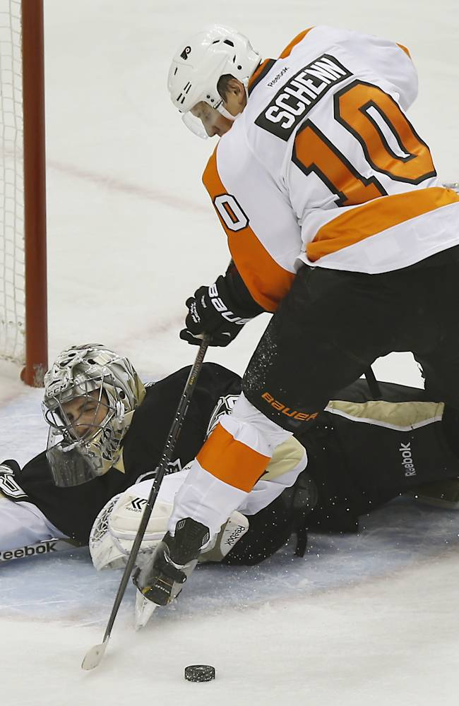 Pittsburgh Penguins goalie Marc-Andre Fleury, left, makes a save on Philadelphia Flyers' Brayden Schenn (10) during the first period of an NHL hockey game on Sunday, March 16, 2014, in Pittsburgh