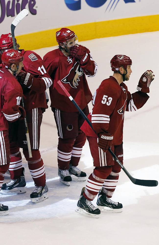Phoenix Coyotes' Mike Ribeiro (63), Derek Morris (53), Antoine Vermete, third from right, Martin Hanzal (11), David Moss (18) goalie Mike Smith, and Oliver Ekman-Larsson celebrate their win over the Edmonton Oilers after an NHL hockey game Saturday, Oct. 26, 2013, in Glendale, Ariz. The Coyotes won 5-4