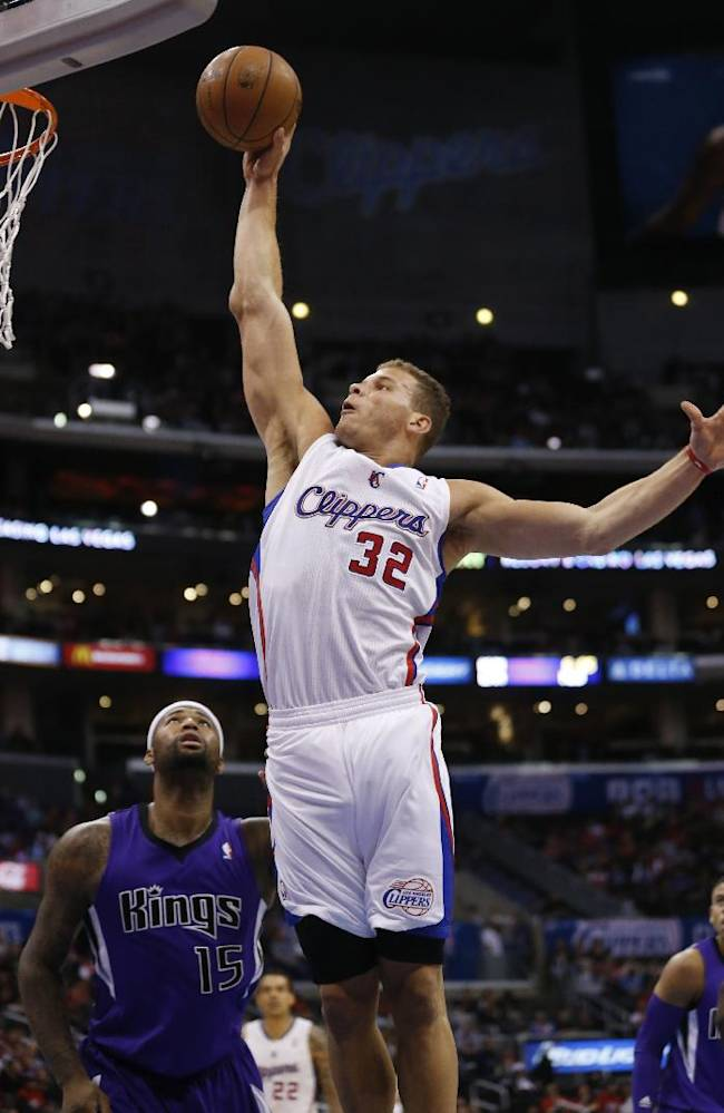 CORRECTS DAY OF WEEK TO SATURDAY - Los Angeles Clippers forward Blake Griffin dunks the ball over Sacramento Kings center DeMarcus Cousins during the first half of an NBA basketball game in Los Angeles, Saturday, April 12, 2014
