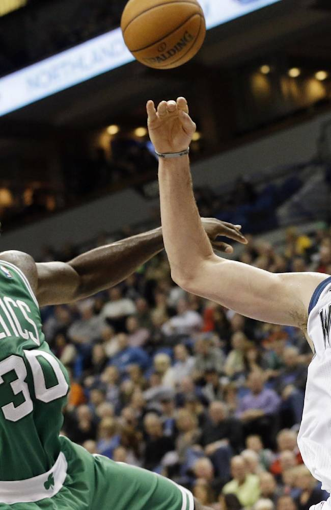 Boston Celtics' Brandon Bass, left, breaks up a rebound-attempt by Minnesota Timberwolves' Kevin Love in the first quarter of an NBA basketball game on Saturday, Nov. 16, 2013, Minneapolis