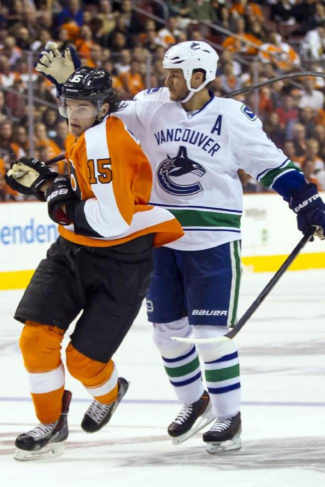 Philadelphia Flyers' Tye McGinn (15) tries to skate past Vancouver Canucks' Kevin Bieksa during the second period of an NHL hockey game, Tuesday, Oct. 15, 2013, in Philadelphia