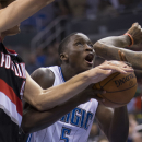 Orlando Magic's Victor Oladipo (5) fights to the basket against Portland Trail Blazers' Robin Lopez, left and Dorell Wright, right during the first half of an NBA basketball game in Orlando, Fla., Tuesday, March 25, 2014 The Associated Press
