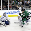Vancouver Canucks' Ryan Miller (30) deflects a shot by Dallas Stars' Kevin Connauton (23) as Canucks' Chris Tanev falls to the ice during the first period of an NHL hockey game, Tuesday, Oct. 21, 2014, in Dallas The Associated Press