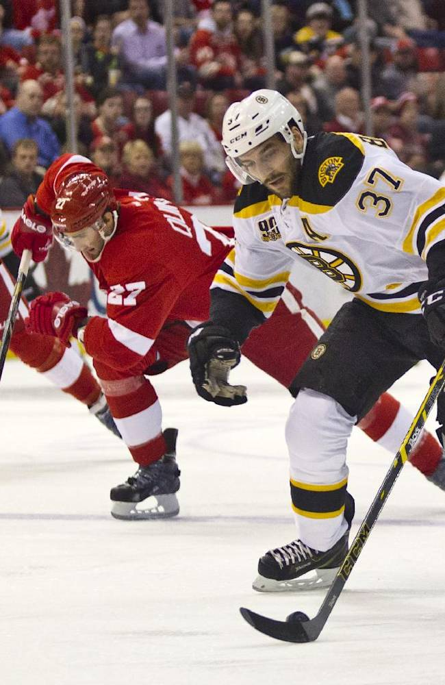 Boston Bruins forward Patrice Bergeron (37) skates with the puck while pursued by Detroit Red Wings defenseman Kyle Quincey (27) and forward Joakim Andersson (63), during the first period of an NHL hockey game in Detroit, Mich., Wednesday, April 2, 2014