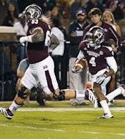 Mississippi State wide receiver Jameon Lewis (4) picks up a blocker in offensive linesman Dillon Day (63) on his way to a 19-yard touchdown run in the first half of their NCAA college football game against Kentucky at Davis Wade Stadium in Starkville, Miss., Thursday, Oct. 24, 2013. (AP Photo/Rogelio V. Solis)