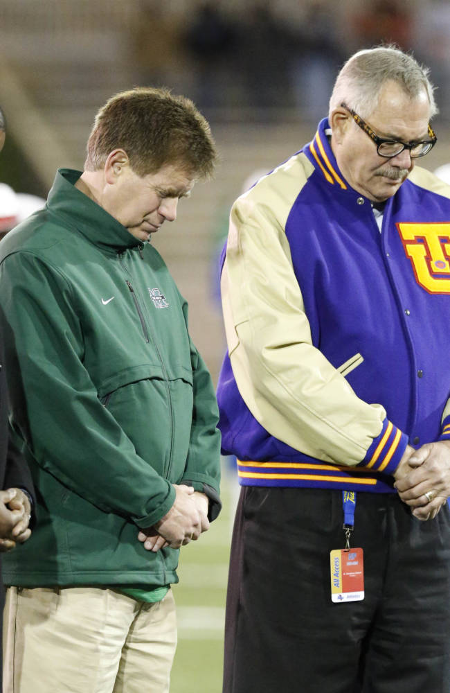 Marshall athletic director Mike Hamrick (center) and Tulsa president Steadman Upham bow their heads to mark the anniversary of the Nov. 14, 1970, plane crash that killed the Marshall football team and others before  a football game against Tulsa at the University of Tulsa in Tulsa, Okla. on Thursday, November 14, 2013. (
