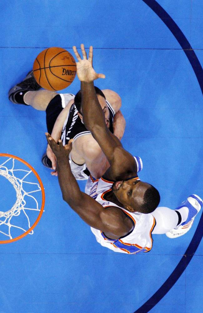 Oklahoma City Thunder forward Serge Ibaka, top, reaches for a rebound over San Antonio Spurs guard Manu Ginobili in the third quarter of Game 3 of an NBA basketball playoff series in the Western Conference finals, Sunday, May 25, 2014, in Oklahoma City. Oklahoma City won 106-97