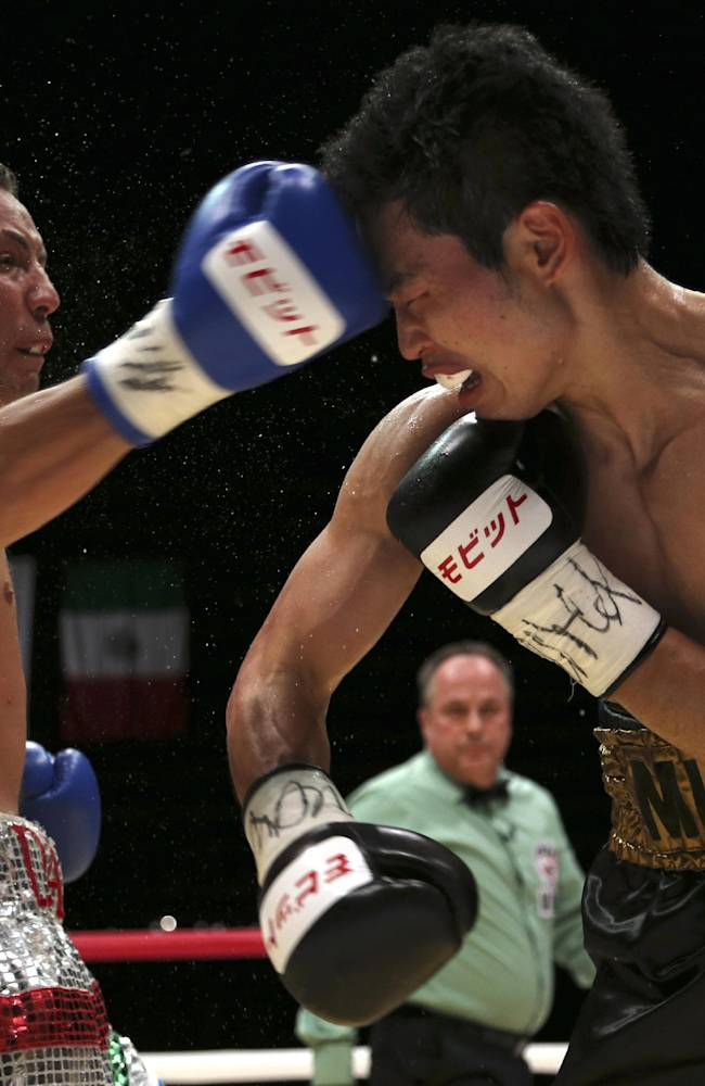 Japanese champion Takashi Miura, right, gets a punch from Mexican challenger Dante Jardon in the fourth round of their WBC super featherweight title bout in Tokyo Tuesday, Dec. 31, 2013. Miura defended his title by a technical knockout in the ninth round