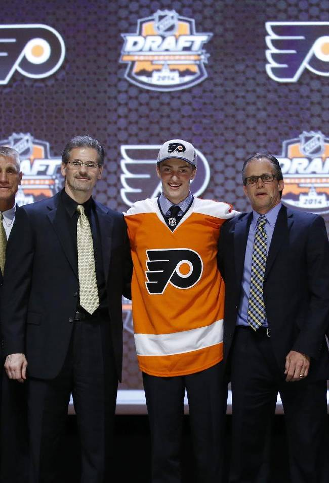 Travis Sanheim stands with Philadelphia Flyers officials after being chosen 17th overall during the first round of the NHL hockey draft, Friday, June 27, 2014, in Philadelphia