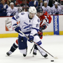 Tampa Bay Lightning right wing Nikita Kucherov (86), from Russia, skates with the puck as Washington Capitals right wing Troy Brouwer (20) defends in the second period of an NHL hockey game on Sunday, April 13, 2014, in Washington The Associated Press