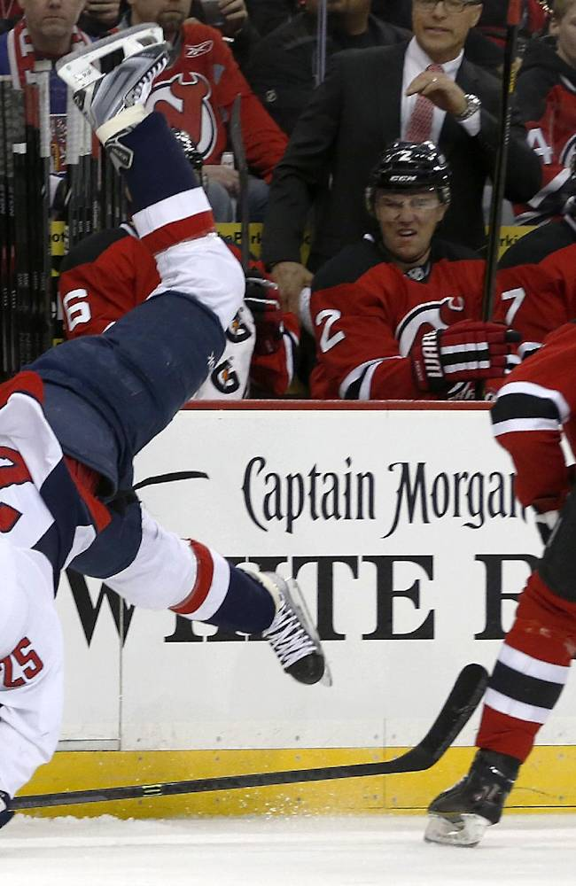 Washington Capitals left wing Jason Chimera, left, falls to the ice after colliding with New Jersey Devils defenseman Adam Larsson, of Sweden, during the first period of an NHL hockey game, Friday, April 4, 2014, in Newark, N.J