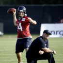Houston Texans quarterback Ryan Fitzpatrick (14) throws as coach Bill O'Brien kneels during an NFL football training camp on Saturday, July 26, 2014, in Houston The Associated Press