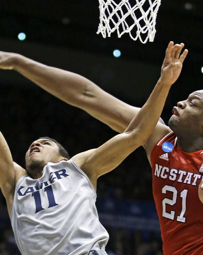 Xavier guard Dee Davis (11) shoots against North Carolina State forward Beejay Anya (21) during the first half of a first-round game of the NCAA college basketball tournament, Tuesday, March 18, 2014, in Dayton, Ohio