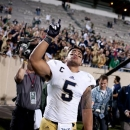 In this Sept. 15, 2012 photo, Notre Dame linebacker Manti Te'o points to the sky as he leaves the field after a 20-3 win against Michigan State in East Lansing, Mich. In a shocking announcement, Notre Dame said Te'o was duped into an online relationship with a woman whose