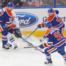 Vancouver Canucks' Dan Hamhuis (2) works for the puck between Edmonton Oilers' Boyd Gordon (27) and Ryan Nugent-Hopkins (93) during the second period of an NHL hockey game Saturday, Nov. 1, 2014, in Edmonton, Alberta The Associated Press