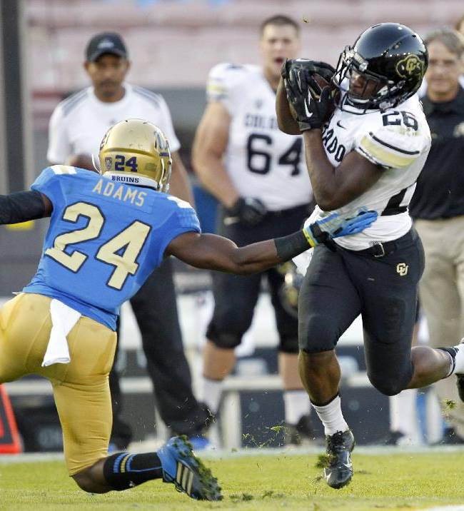 Colorado running back Tony Jones (26) eludes UCLA cornerback Ishmael Adams (24) after making a catch in the first half of their NCAA college football game Saturday, Nov. 2, 2013, in Pasadena, Calif