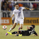 D.C. United's Lewis Neal, right, slide tackles Los Angeles Galaxy's Alan Gordon, left, during the first half of an MLS soccer match on Wednesday, Aug. 27, 2014, in Carson, Calif The Associated Press