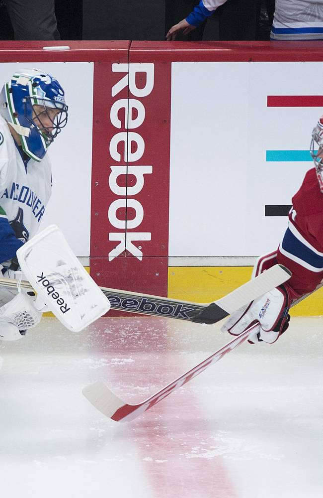 Montreal Canadiens goaltender Carey Price, right, and Vancouver Canucks goalie Roberto Luongo touch sticks prior to an NHL hockey game in Montreal, Thursday, Feb. 6, 2014. Both goalies are on the Canadian Olympic team