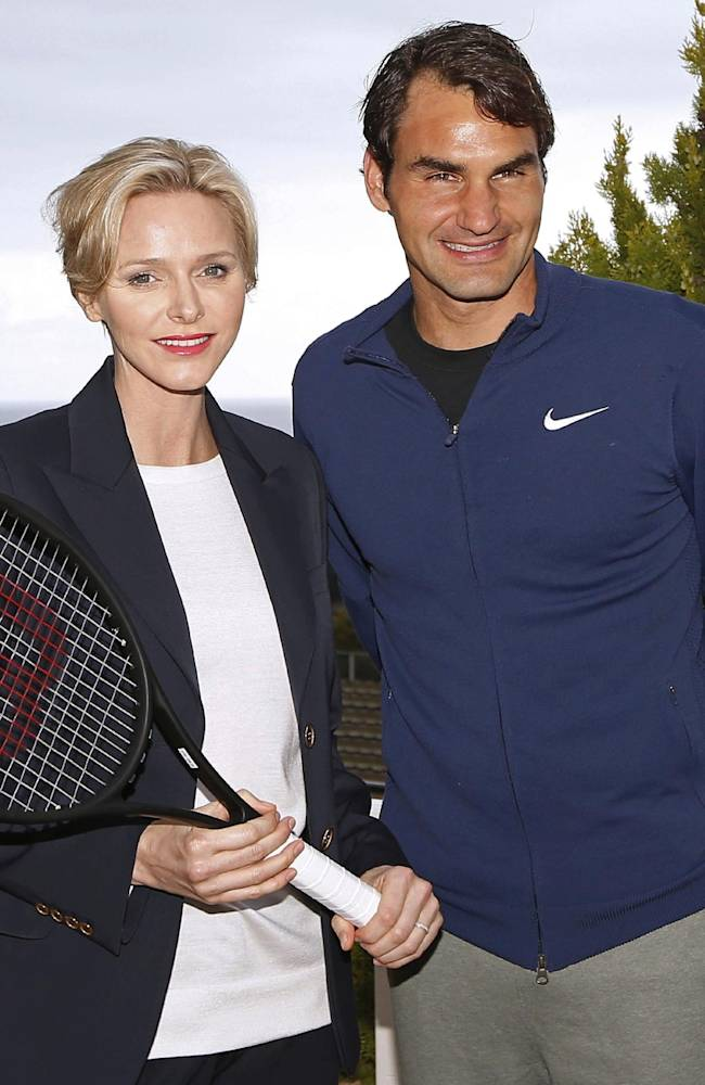 Princess Charlene of Monaco, left, and Swiss tennis player Roger Federer, right, pose for photographers during the Monte Carlo Tennis Masters tournament in Monaco, Friday, April 18, 2014. The princess received a signed tennis racket from the hands of Federer. The racket will be sold at auction and the proceeds will be given to the Princess Charlene of Monaco foundation, which aims to promote sports activities as a vector for education and the development of children