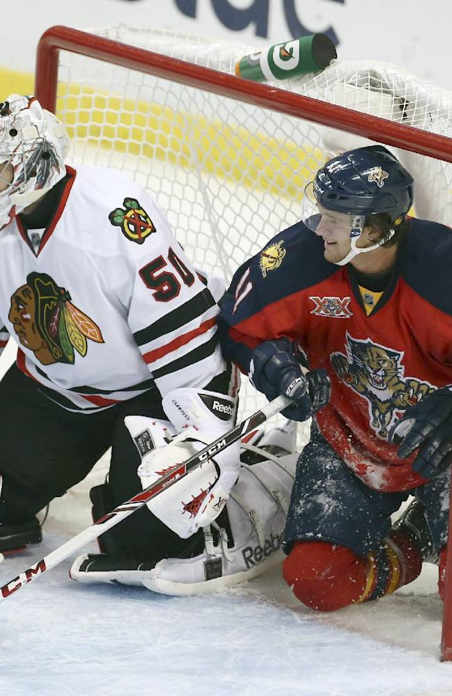 Florida Panthers' Jonathan Hueberdeau (11) slides into the goal and watches game action with Chicago Blackhawks' goalie Corey Crawford (50) during the second period of an NHL hockey game in Sunrise, Fla., Tuesday, Oct. 22, 2013