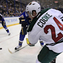 Minnesota Wild's Matt Cooke (24) passes the puck around St. Louis Blues' Carlo Colaiacovo and Patrik Berglund, left, of Sweden, during the first period of an NHL hockey game Monday, Nov. 25, 2013, in St. Louis The Associated Press